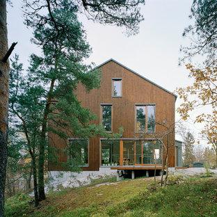Foto de fachada marrón, escandinava, extra grande, de tres plantas, con revestimiento de madera y tejado a dos aguas