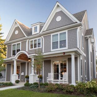 На фото: серый частный загородный дом в стиле шебби-шик с облицовкой из ЦСП, двускатной крышей и крышей из гибкой черепицы с