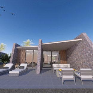 他の地域の小さいビーチスタイルのおしゃれな家の外観 (石材サイディング、グレーの外壁、混合材屋根) の写真