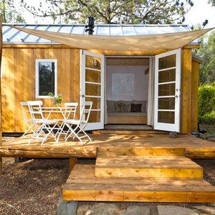 Esempio della facciata di una casa piccola marrone contemporanea con rivestimento in legno e tetto a capanna