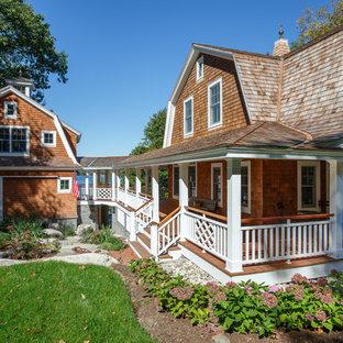 Ejemplo de fachada marrón, costera, de dos plantas, con tejado a doble faldón y revestimiento de madera