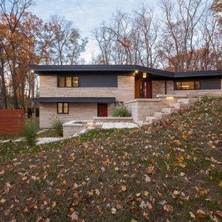 Cette image montre une façade de maison grise vintage de taille moyenne et à un étage avec un revêtement en panneau de béton fibré et un toit plat.