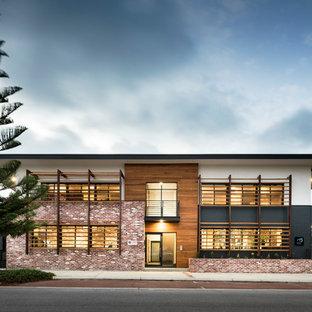 Idéer för att renovera ett stort funkis flerfärgat hus, med två våningar, platt tak och tak i metall