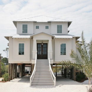 Example of a mid-sized coastal white two-story wood exterior home design in Miami with a hip roof