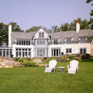 Foto på ett stort maritimt beige hus, med tre eller fler plan, stuckatur och sadeltak