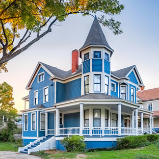 Huge victorian blue three-story wood exterior home idea in Other with a shingle roof
