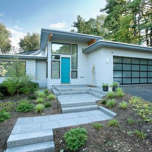 Imagen de fachada de casa blanca, vintage, de tamaño medio, de una planta, con tejado plano y revestimiento de vinilo