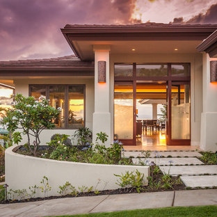 Large island style beige two-story stucco house exterior photo in Hawaii with a hip roof and a tile roof