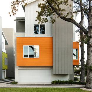Idée de décoration pour une façade de maison orange design à deux étages et plus avec un revêtement mixte.