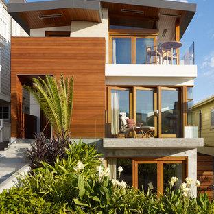 Foto della facciata di una casa unifamiliare tropicale a tre piani di medie dimensioni con rivestimento in legno e copertura in metallo o lamiera