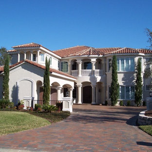 Example of a large tuscan black two-story stucco exterior home design in Jacksonville with a hip roof