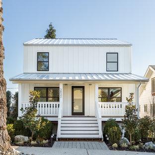 Ejemplo de fachada blanca, campestre, de dos plantas, con revestimiento de metal y tejado a dos aguas