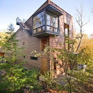 Неиссякаемый источник вдохновения для домашнего уюта: деревянный, трехэтажный, коричневый, большой частный загородный дом в современном стиле с односкатной крышей и зеленой крышей