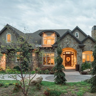 Traditional beige two-story stone exterior home idea in Salt Lake City with a hip roof