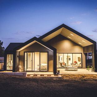 Foto de fachada de casa negra, minimalista, de una planta, con revestimientos combinados, tejado a dos aguas y tejado de metal