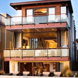 ロサンゼルスのコンテンポラリースタイルのおしゃれな三階建ての家 (石材サイディング、陸屋根、戸建、混合材屋根、マルチカラーの外壁) の写真