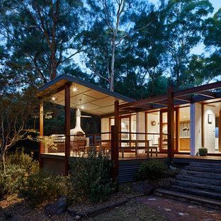 Imagen de fachada de casa blanca, vintage, de tamaño medio, a niveles, con revestimiento de hormigón, tejado a la holandesa y tejado de metal