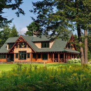 Inspiration pour une très grand façade de maison marron chalet à un étage avec un toit à croupette et un toit végétal.