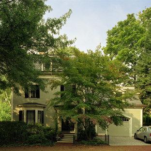 Modelo de fachada de casa verde, clásica renovada, de tamaño medio, de dos plantas, con revestimiento de madera, tejado a cuatro aguas y tejado de teja de madera