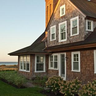 Ejemplo de fachada marrón, tradicional, de dos plantas, con revestimiento de madera y tejado a dos aguas