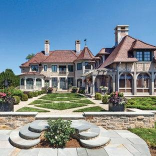 Imagen de fachada de casa beige, ecléctica, extra grande, de tres plantas, con revestimientos combinados, tejado a cuatro aguas y tejado de teja de barro