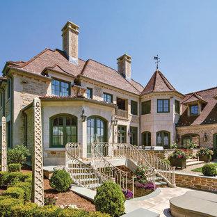 Imagen de fachada de casa beige, bohemia, extra grande, de tres plantas, con revestimientos combinados, tejado a cuatro aguas y tejado de teja de barro