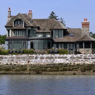 Modelo de fachada verde, clásica, grande, de tres plantas, con revestimiento de madera y tejado a cuatro aguas