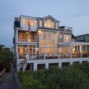 Diseño de fachada beige, costera, grande, de tres plantas, con revestimiento de madera