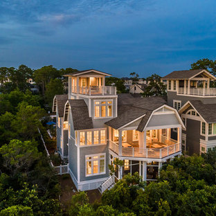 Huge beach style blue three-story house exterior photo in Other with a gambrel roof