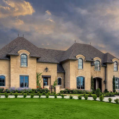 Inspiration for a large timeless beige two-story brick house exterior remodel in Little Rock with a shingle roof