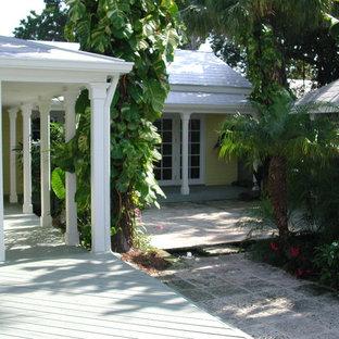 Idee per la facciata di una casa ampia gialla tropicale a un piano con rivestimento in legno