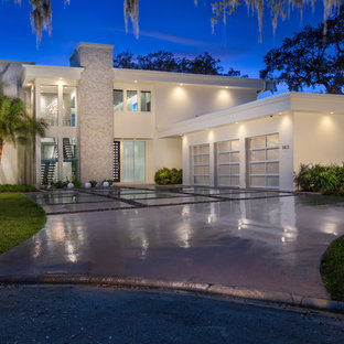 Example of a large minimalist white two-story stucco flat roof design in Jacksonville