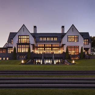 Réalisation d'une très grand façade de maison blanche tradition à deux étages et plus avec un revêtement mixte et un toit mixte.