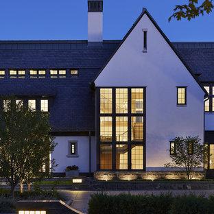 Aménagement d'une très grand façade de maison blanche classique à deux étages et plus avec un revêtement mixte et un toit mixte.