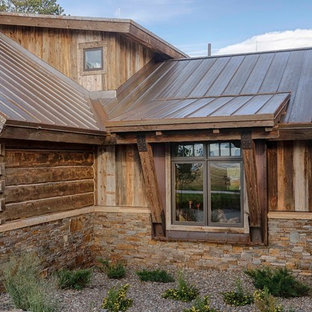 Example of a mountain style brown mixed siding exterior home design in Other with a metal roof