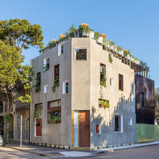 Diseño de fachada beige, ecléctica, de tres plantas, con tejado plano y techo verde
