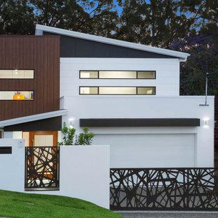 Modern inredning av ett stort vitt hus, med två våningar, tegel och tak i metall