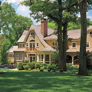Mid-sized ornate beige two-story wood house exterior photo in Boston with a clipped gable roof and a shingle roof
