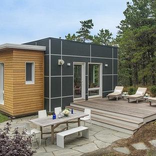 Foto de fachada de casa negra, moderna, pequeña, de dos plantas, con revestimiento de aglomerado de cemento y tejado plano