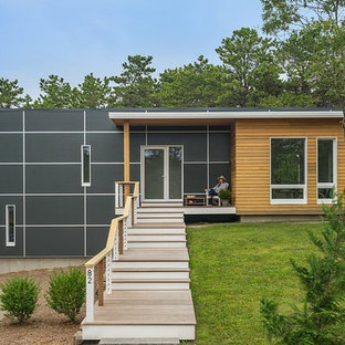 This is an example of a small contemporary two-storey black house exterior in Boston with a flat roof and mixed siding.