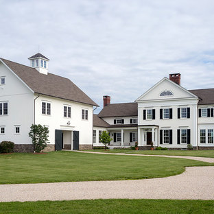 Large cottage white two-story wood exterior home photo in Bridgeport with a shingle roof