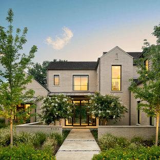 Imagen de fachada de casa beige, actual, de dos plantas, con tejado de teja de madera