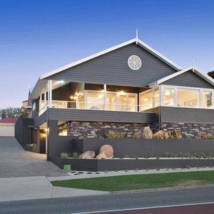 Imagen de fachada de casa gris, costera, a niveles, con revestimientos combinados y tejado a dos aguas