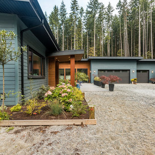 Example of a huge minimalist blue two-story concrete fiberboard house exterior design in Vancouver with a shed roof and a metal roof