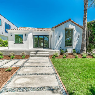 Example of a mid-sized tuscan white one-story stucco exterior home design in Los Angeles with a tile roof