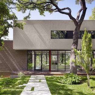 Inspiration for a contemporary brown two-story stone exterior home remodel in Austin