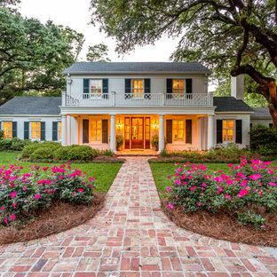 Imagen de fachada de casa blanca, clásica, extra grande, de dos plantas, con tejado a dos aguas y tejado de teja de madera