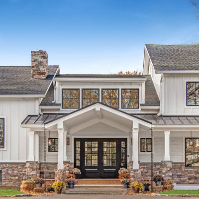 Large country white two-story concrete fiberboard exterior home idea in New York with a mixed material roof