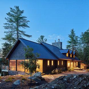 Modelo de fachada de casa marrón, rústica, grande, a niveles, con revestimiento de madera, tejado a dos aguas y tejado de metal