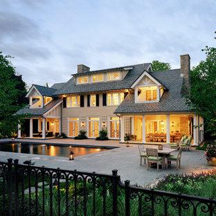 Пример оригинального дизайна: большой, трехэтажный, бежевый частный загородный дом в классическом стиле с двускатной крышей, облицовкой из цементной штукатурки и крышей из гибкой черепицы